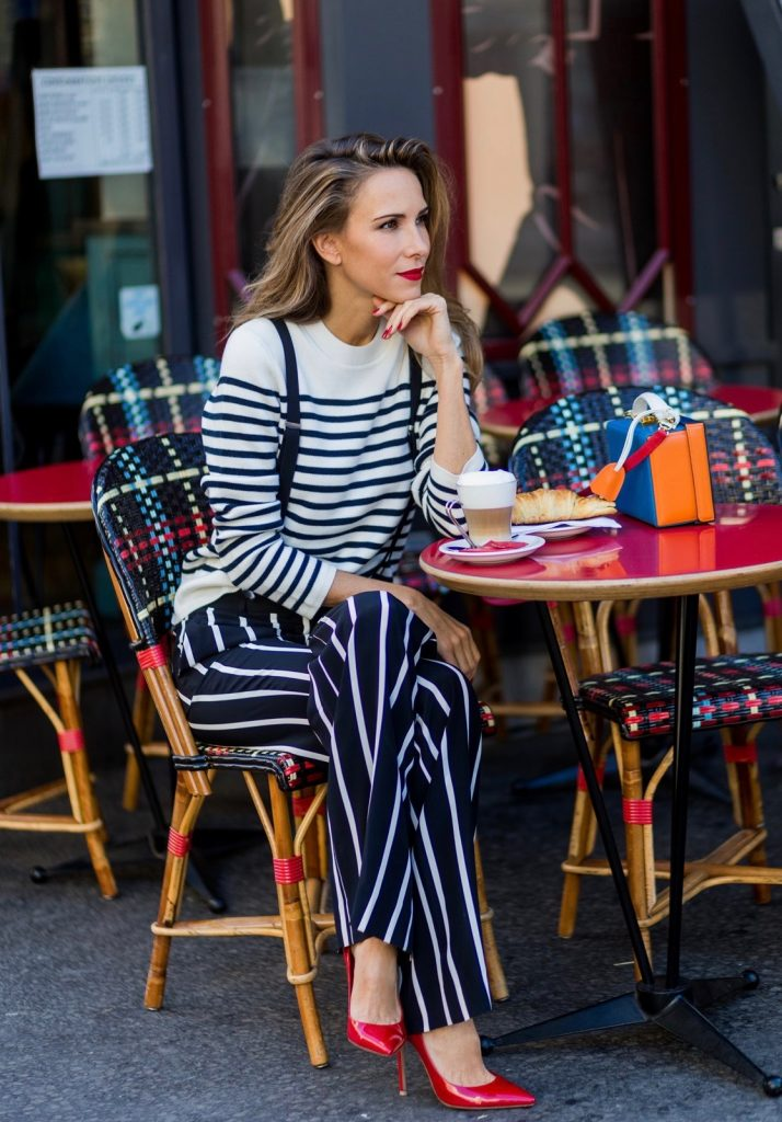 PARIS, FRANCE - OCTOBER 01: German model and fashion blogger Alexandra Lapp (@alexandralapp_) sitting in a French Cafe drinking coffee and eating Croissant wearing striped jumper from Steffen Schraut, striped pants from Emilio Pucci, suspenders H&M, Gianvito Rossi shoes and Mark Cross bag on October 1, 2016 in Paris, France. (Photo by Christian Vierig/Getty Images) *** Local Caption *** Alexandra Lapp