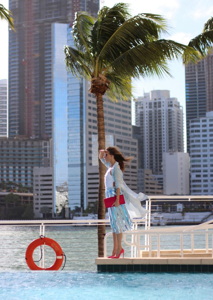 MANDARIN ORIENTAL; MIAMI; FLORIDA - JANUARY : German model and fashion blogger Alexandra Lapp (@alexandralapp_) wearing a light blue trenchcoat, a pleated skirt in metallic blue and a body from Patrizia Pepe, pink pumps and pink silk clutch by Prada and sunglasses from Le Specs on January, 2017 in Miami *** Local Caption *** Alexandra Lapp