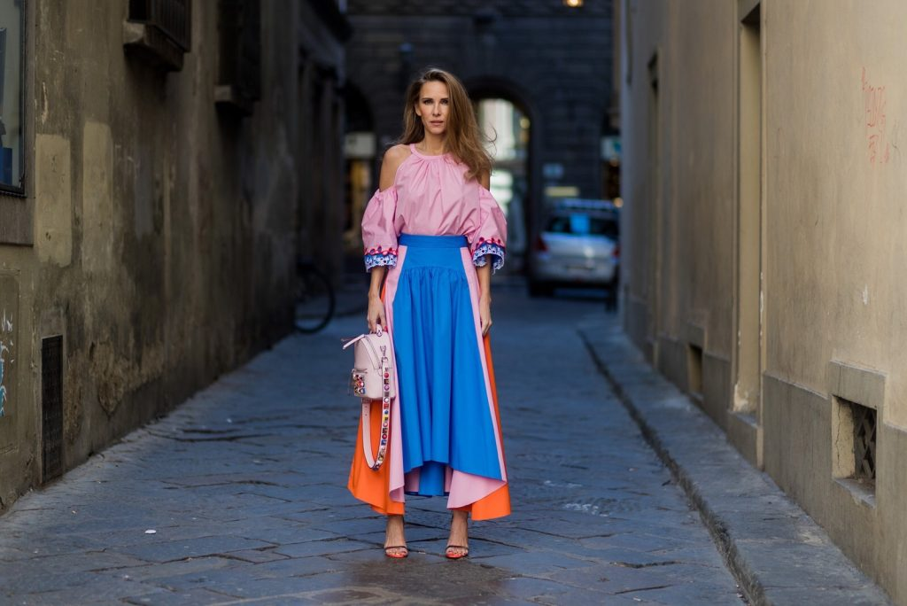 FLORENCE, ITALY - JANUARY 11: German fashion blogger and model Alexandra Lapp is wearing off-the-shoulder embroidered cotton-poplin blouse by Peter Pilotto, asymmetric cotton-poplin skirt by Peter Pilotto (this skirt is made from panels of bright-blue, baby-pink and bright-orange cotton-poplin and is cut with an asymmetric midi hem), Fendi baby pink leather shoulder bag embellished with colorful pyramid studs and adjustable shoulder strap, 'Chiara' Butterfly style sandals from Sophia Webster ( printed Butterfly Wing sandal, finished with a silver mirror front strap) on January 11, 2017 in Florence, Italy. (Photo by Christian Vierig/Getty Images) *** Local Caption *** Alexandra Lapp