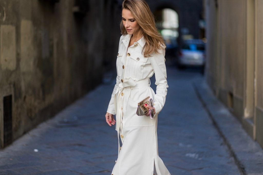FLORENCE, ITALY - JANUARY 11: German fashion blogger and model Alexandra Lapp is wearing trenchcoat dress in white with golden buttons waisted with a belt from Talbot Runhof, Chanel mules and Chanel box clutch bag in gold (as seen on Carrie Bradshaw (Sarah Jessica Parker) in Sex and the City 2, sunglasses from Les Specs on January 11, 2017 in Florence, Italy. (Photo by Christian Vierig/Getty Images) *** Local Caption *** Alexandra Lapp