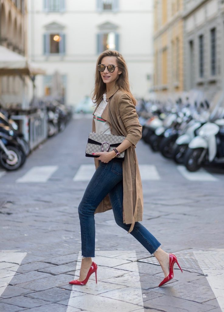 FLORENCE, ITALY - JANUARY 11: German fashion blogger and model Alexandra Lapp is wearing retro vibe Gucci printed cotton T-shirt, featuring a throwback Gucci logo, this piece features distressed detailing around the neckline, slim fit Wedgie Icon Fit Jeans from Levi's, suede /buckskin leather trench coat from Oui, Dionysus GG Supreme Medium Gucci shoulder bag, Le Specs sunglasses, red pumps from Gianvito Rossi on January 11, 2017 in Florence, Italy. (Photo by Christian Vierig/Getty Images) *** Local Caption *** Alexandra Lapp