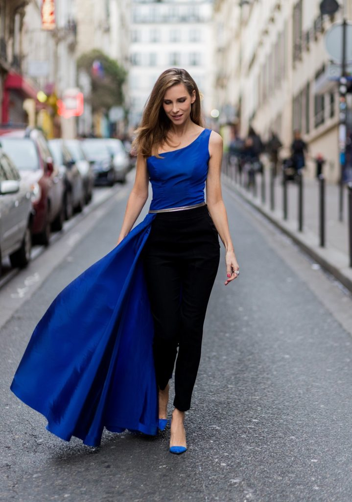 PARIS; FRANCE; Model and Blogger Alexandra Lapp wearing asymmetric one shoulder silhouette, blue taffeta and leather top from Pearl and Rubies with a skin barring asymmetric one-shoulder Silhouette, Black pants from Pearl and Rubies, Blue suede plexi pumps from Gianvito Rossi, Catherine shoulder mini bag in silver from MCM on March 4, 2017 in Paris, France.