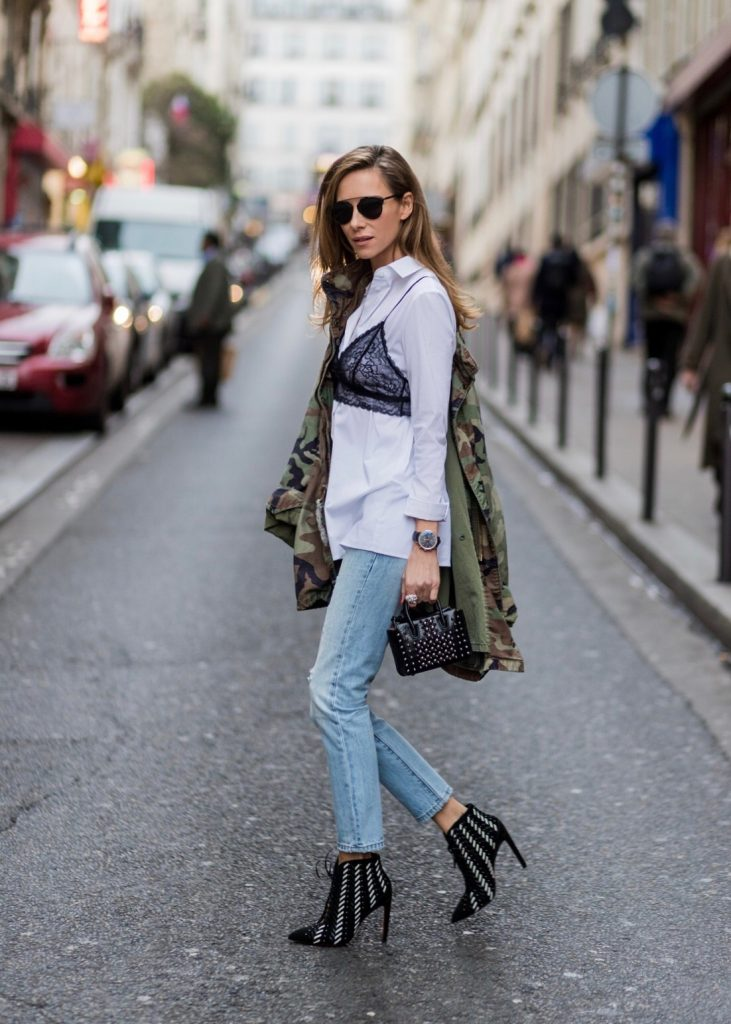 PARIS; FRANCE; Model and Blogger Alexandra Lapp wearing Bra over shirt trend, a light blue Levi's 501 Skinny Jeans with button fly in the classic five-pocket design, signature Levi's tab and arch are stitches on back pockets, white blouse from Acne Studios, Bust Candy Bra Top by FARINA for NA-KD in black features adjustable satin shoulder straps, Mills pearl studs tote bag from MCM in black with hand-applied faux pearls, black and white Santoni ankle boots in suede, original vintage camouflage, army jacket, ring from Cartier on March 4, 2017 in Paris, France.
