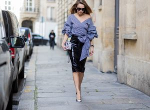 PARIS; FRANCE; Model and Blogger Alexandra Lapp wearing latex skirt and ruched sleeve top, a black Couture Latex Crystal pencil Skirt from Atsuko Kudo, Pepita blouse top from Storets with black and white check print, Decollete neckline and riches sleeve Black and white pumps from Saint Laurent, Oversized Audrey sunglasses from Celine, Black and white 2.55 bag in tweed from Chanel on March 3, 2017 in Paris, France.