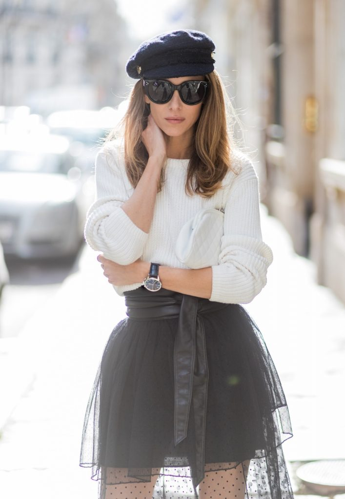 PARIS; FRANCE; Blogger and Model Alexandra Lapp rock dots by wearing knit Oui Black Lace Layer Skirt from Storets with layers of differently patterned sheer fabrics, a classic skater style silhouette with lace and dotted patterns cascading down below the leg, Leather waist belt - Set Fashion, Socks - vintage, Pumps - white snake pumps from Christan Louboutin, Sunglasses - Celine Audrey, Clutch - Chanel on March 3, 2017 in Paris, France.