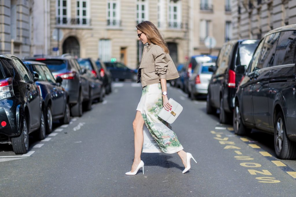 PARIS; FRANCE MARCH 03, Model and Blogger Alexandra Lapp wearing Stella McCartney long viscose cady skirt in cream landscape print, Stella McCartney blouse / Aspen boxy style shirt in cream featuring a landscape print., Stella McCartney Short oversized cotton bomber jacket in khaki featuring a pointed collar and zip through front. Cropped style featuring dropped shoulders, flap front pot keys and elasticated hemline and cuffs with a contrasting metallic trim, Black and white Balmain belt, White lacquer pumps from Prada on March 3, 2017 in Paris, France.