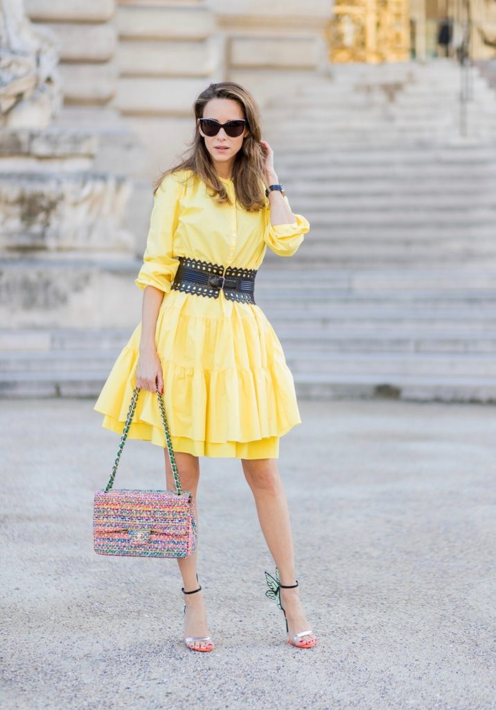 PARIS, FRANCE - MARCH 03: Alexandra Lapp wearing a yellow sunshine dress by Marc Cain, loose-fitting dress with flounce-like tiers, narrow, single-buttoned,(waist belt) Azzedine Alaia, Chiara Butterfly style sandals from Sophia Webster ( printed Butterfly Wing sandal, finished with a silver mirror front strap), cat eye sunglasses with pearls from Chanel, Chanel bag on March 3, 2017 in Paris, France. (Photo by Christian Vierig/Getty Images)