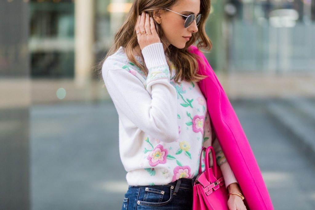 Model and fashion blogger Alexandra Lapp wearing a cashmere pullover from Heartbreaker with precious details of sewed on colorful pastel flowers, slim fit high waist denim from Rag & Bone, a pink wool and cashmere coat by Prada, turquoise pumps with a silver tip from Manolo Blahnik, Le Specs sunglasses and the Mini Birkin bag in electric pink and calf leather with fold-over closure from Hermes on March 30, 2017 in Duesseldorf, Germany.