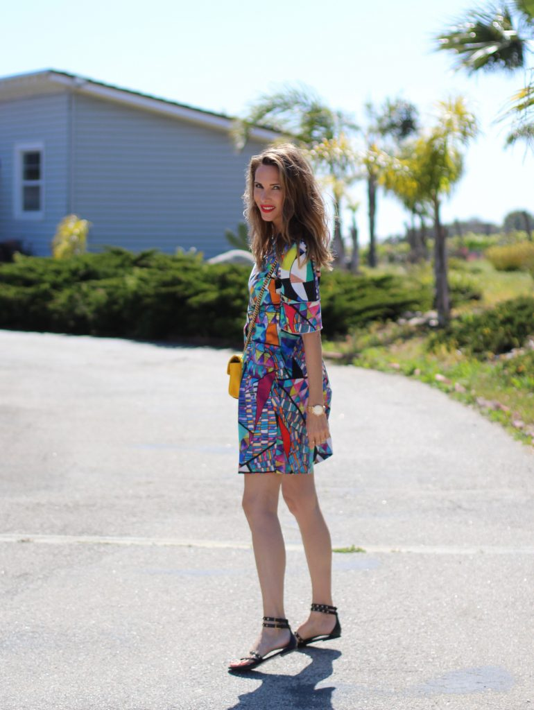Malibu, Los Angeles; Model and fashion blogger Alexandra Lapp wearing a colorful dress by La Martina, the Polo brand, sandals from Saint Laurent in black with golden rock studs, red lipstick from MAC, a yellow Gucci GG Marmont bag, IWC Da Vinci Automatic 36 watch in 18-carat red gold with diamonds and jewelry from AYS (Art Youth Society) in Malibu on April 17, 2017 in Los Angeles, California.
