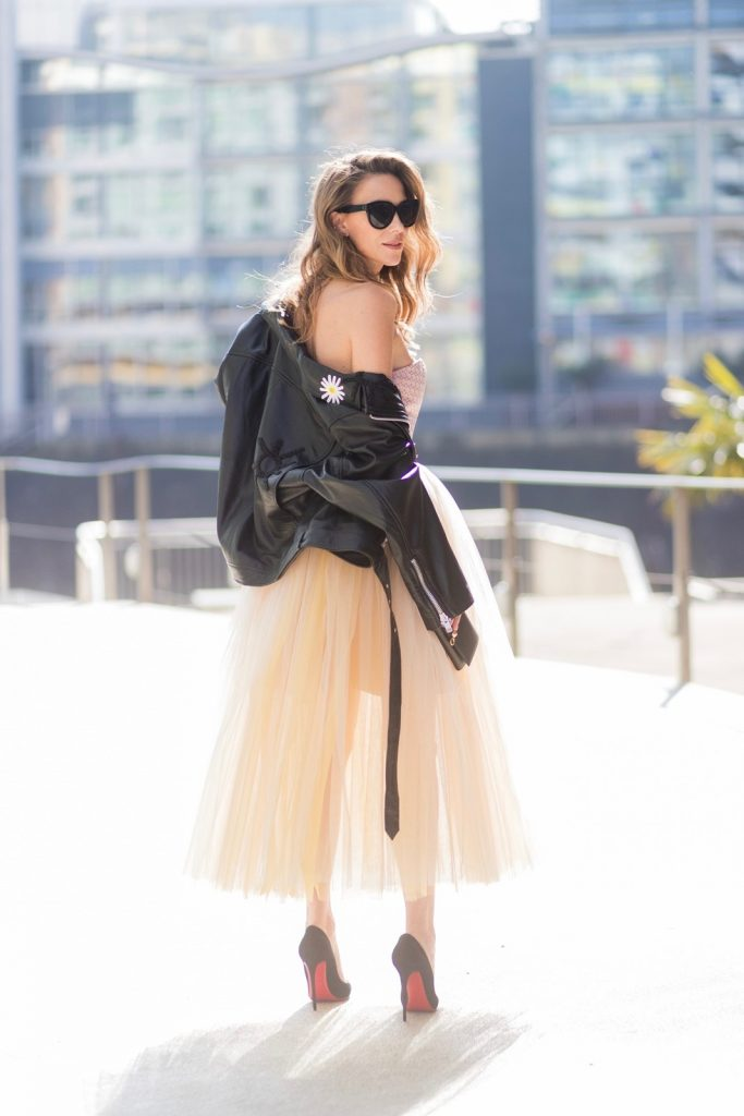 Model and fashion blogger Alexandra Lapp wearing a Carrie Bradshaw style, a multicolored sleeveless brocade tulle dress from Natasha Zinko, a black biker leather jacket with sewed on flowers with pearl applications from Natasha Zinko, black suede So Kate pums from Christian Louboutin, and black sunglasses from Celine on March 30, 2017 in Duesseldorf, Germany.
