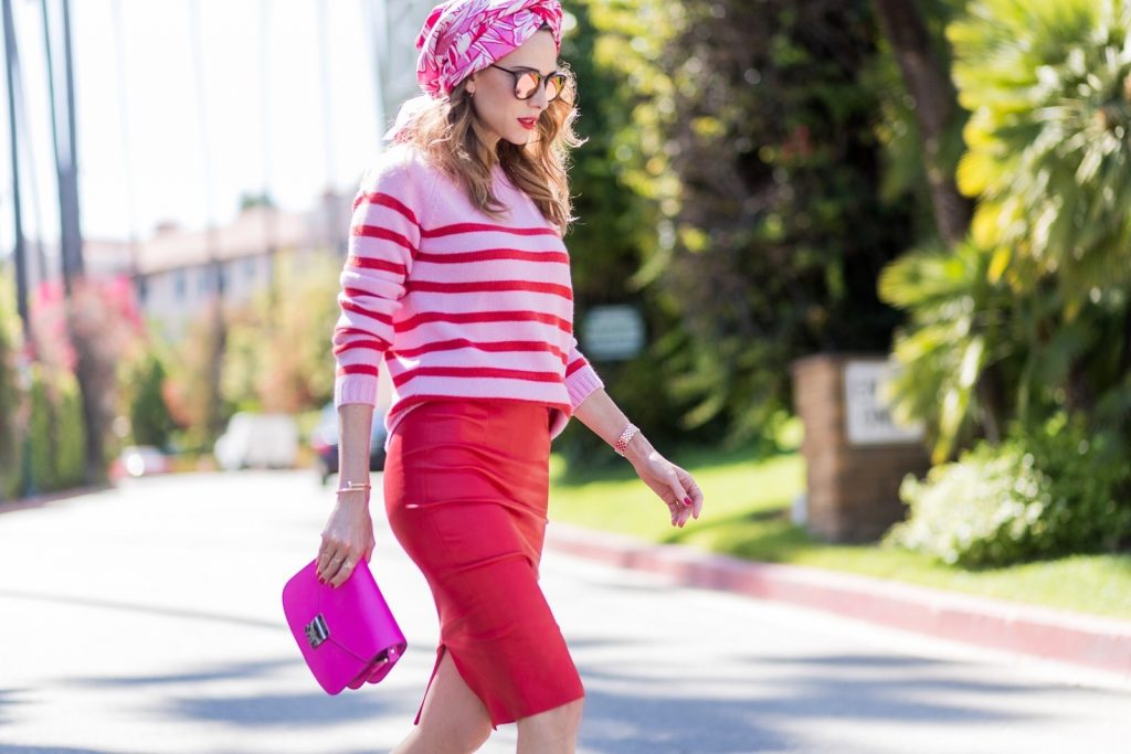 Model and fashion blogger Alexandra Lapp wearing a scarf as a bandana from Heartbreaker, a red stretch leather pencil skirt from American Retro, pink and red striped cashmere pullover by Heartbreaker, red lacquer pumps from Gianvito Rossi, an electric-pink Patricia bag, a small crossbody in vachetta leather, complete with a well-organized interior lined in orange sueded nylon, sunglasses from Le Specs, IWC Da Vinci Automatic 36 watch in 18-carat red gold with diamonds and jewelry from AYS (Art Youth Society) on April 20, 2017 in Los Angeles, California.
