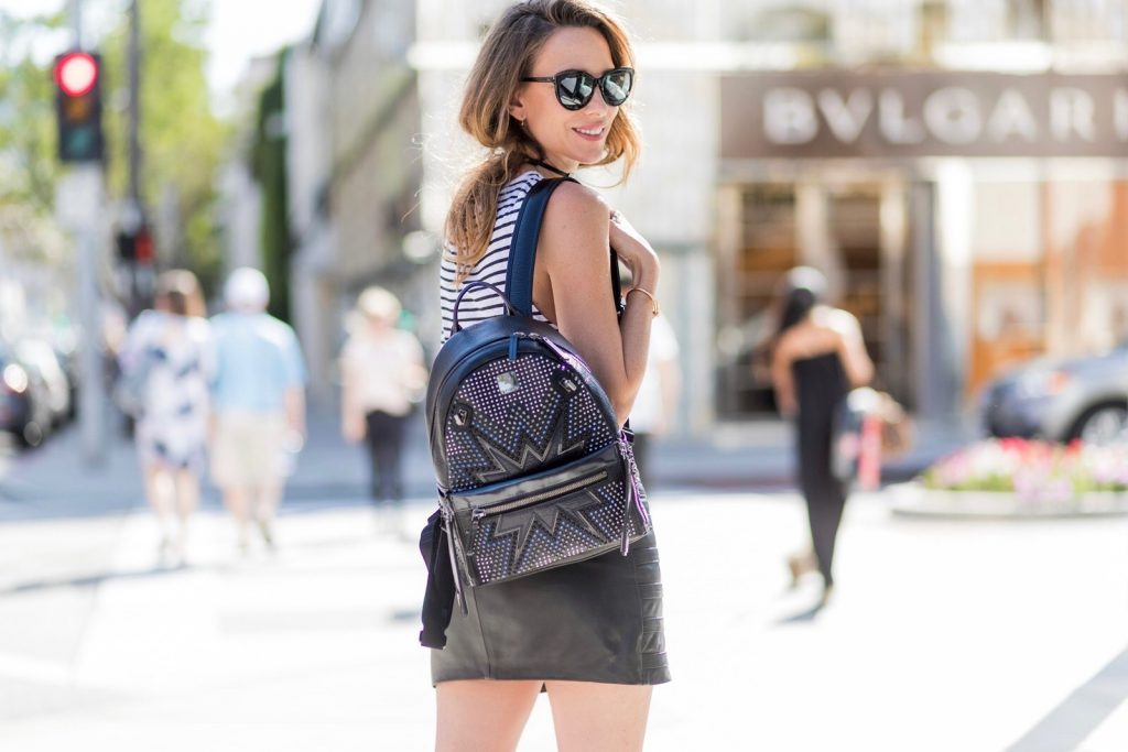 Model and fashion blogger Alexandra Lapp wearing an MCM backpack, high waist mini skirt in black leather with silver buckles from Manokhi Leather, white linen striped zipped top from Karl Lagerfeld, with a leather sunglasses application, Dior Slingback pumps in black patent calfskin leather and J'Adior ribbon with a 10 cm heel, Dior choker around the neck, Diormania sunglasses by Dior, Saint Laurent jacket and the Dual Stark Cyber backpack from MCM with techno-graphic details, made from specially foil-coated black razor cowhide, polished off with applications and studs a plus the front pocket zips off to create a separate crossbody or clutch, IWC Da Vinci Automatic 36 watch in 18-carat red gold with diamonds and jewelry from AYS (Art Youth Society) on April 20, 2017 on Rodeo Drive in Los Angeles, California.