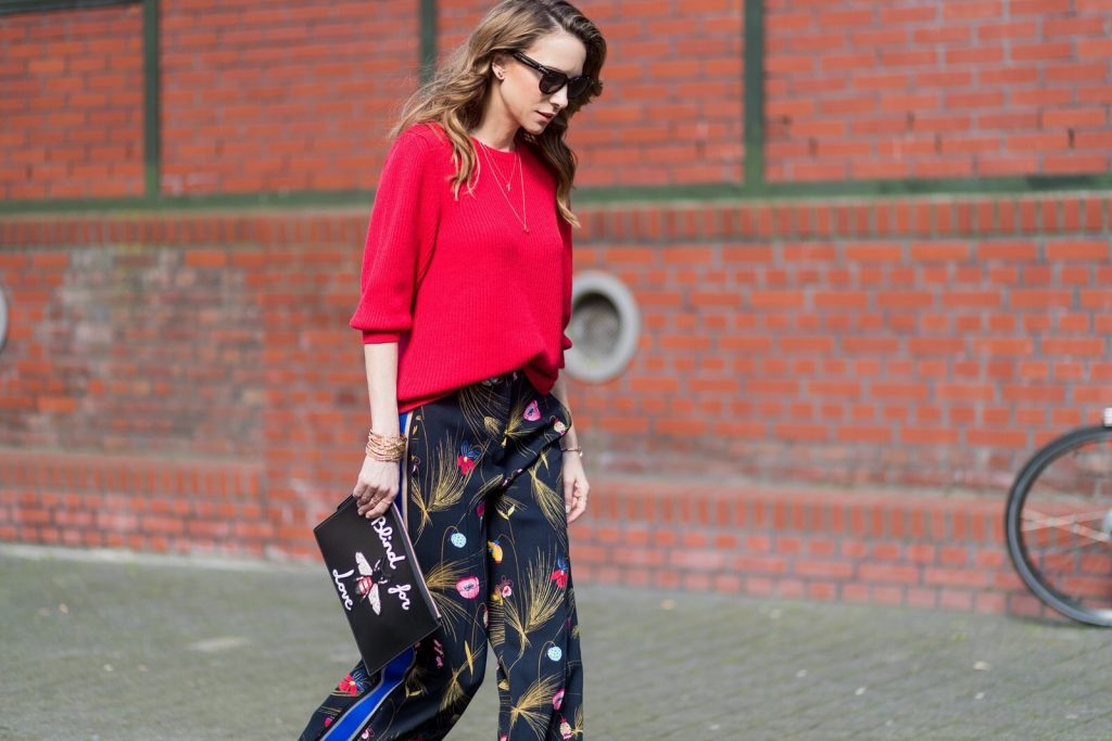 Model and fashion blogger Alexandra Lapp wearing marlene pants, a black and multicoloured floral print trousers from Fendi featuring a high rise, a concealed front fastening, side pockets, applique stripes at the sides, creases and a wide leg, red cashmere knitwear by Valentino, black suede So Kate pumps from Christian Louboutin, gold plated cuff from Gas Bijoux, Celine sunglasses and a black leather ring detail continental purse bag or wallet from Fendi featuring an embossed logo, a press stud fastening, multiple interior card slots, an interior zipped compartment and a gold-tone chain shoulder strap. on March 30, 2017 in Duesseldorf, Germany.