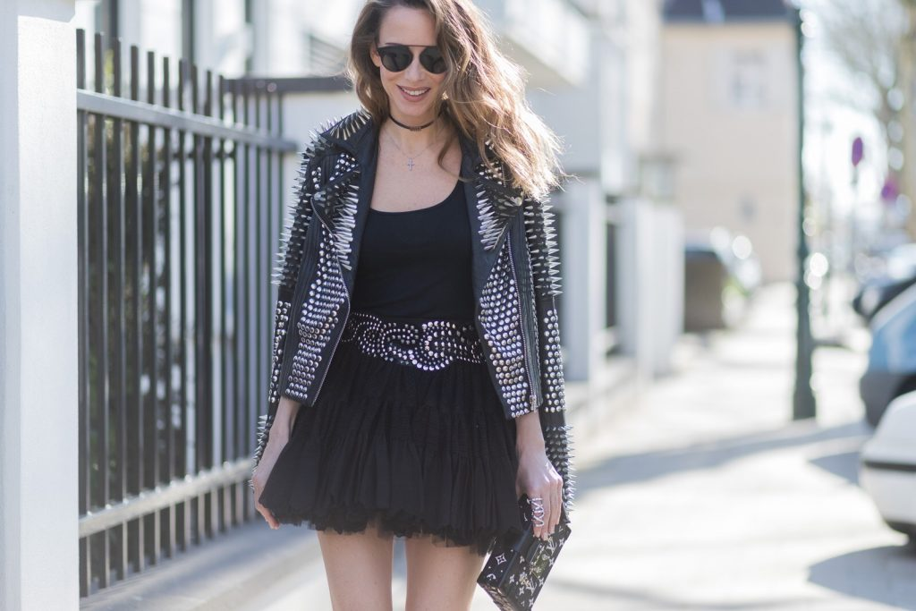 Model and fashion blogger Alexandra Lapp wearing rock style, a black leather jacket from Tigha decorated with studs and little spikes, a vintage black petticoat skirt from Balmain with a belt also decorated with studs, a black tank top from James Perse, black suede sandals embellished with glittery details on the back from Aquazzura x Olivia Palermo, a black and white Petite Malle bag from Louis Vuitton and the brands suitcase shape, a crystal double ring from Giuseppe Zanotti and mirrored sunglasses in black by Saint Laurent on March 30, 2017 in Duesseldorf, Germany.