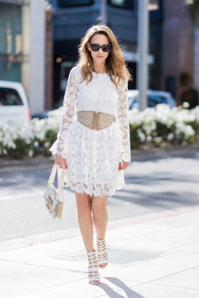 Model and fashion blogger Alexandra Lapp wearing the Roger Vivier Viv' bag which is crafted from linen with lace detailing and features a new slightly rounded buckle and a leather strap, white Zouze dress, waist belt in beige and white leather from Azzedine Alaia, white sandals from Azzedine Alaia, Chanel sunglasses with pearls, IWC Da Vinci Automatic 36 watch in 18-carat red gold with diamonds and jewelry from AYS (Art Youth Society) on April 20, 2017 in Los Angeles, California.