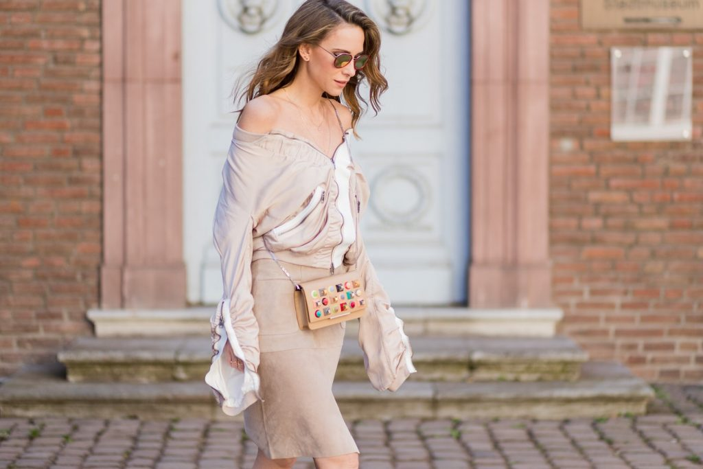 Model and fashion blogger Alexandra Lapp wearing the color powder, a bomber jacket by Tigha which has a slightly shimmering fabric with feminine ruffled parts and sporty elastic pipes and zip details to create an urban look,leather skirt in beige from Steffen Schraut, sandals made of linen with a rose application, sunglasses from Thom Browne, filigree rose gold jewelry from Art Youth Society and a studded embellished crossbody bag from Fendi featuring a foldover top with magnetic closure, an interior zipped compartment, multiple interior card slots and a silver-tone chain shoulder strap on March 30, 2017 in Duesseldorf, Germany.
