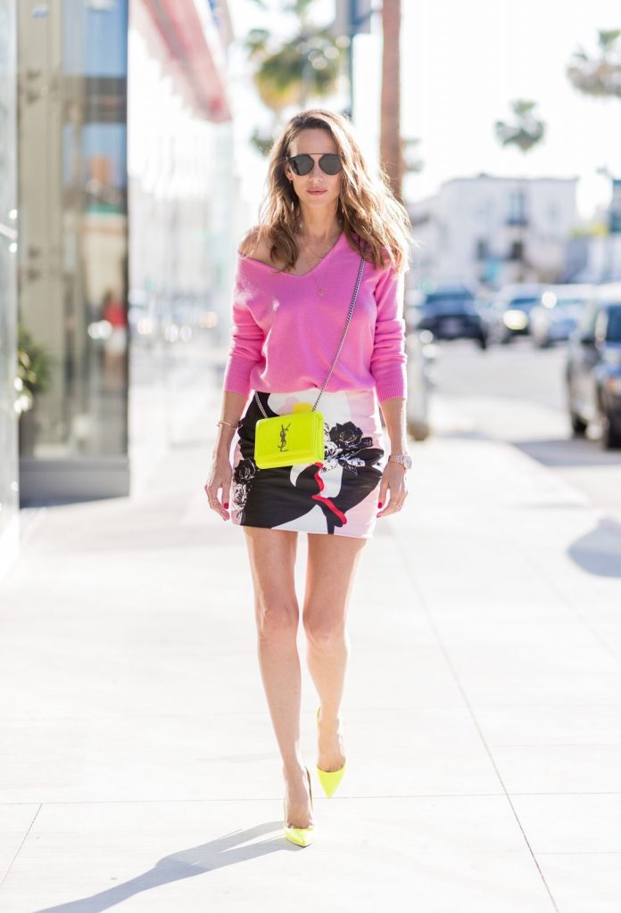 Model and fashion blogger Alexandra Lapp ' think pink ', wearing a multicolor mini leather skirt by Prabal Gurung, pink V neck cashmere pullover from Heartbreaker, neon yellow 'So Kate' pumps from Christian Louboutin, small sunset monogram Saint Laurent leather bag in neon yellow with YSL letters, Dior sunglasses so real in all black, IWC Da Vinci Automatic 36 watch in 18-carat red gold with diamonds and jewelry from AYS (Art Youth Society) on April 20, 2017 in Los Angeles, California.