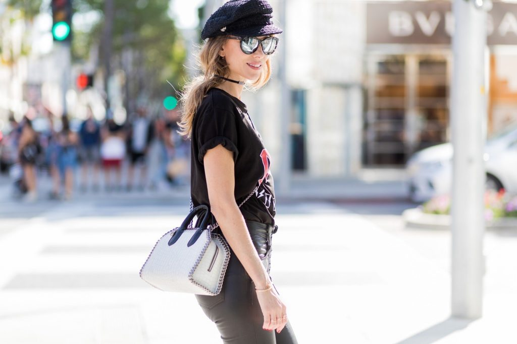 Model and fashion blogger Alexandra Lapp wearing V-Neck-Pumps, a LACE FRONT SKINNY LEATHER PANTS by Unravel, Dior High Voltage T-Shirt from Ecntrc, black and white vegan patent Stella McCartney check pointed toe V-neck-pumps with high-cut toe box, Falabella Box mini faux-leather cross-body bag in black and white, Chanel cap, Diormania sunglasses by Dior and Dior choker, IWC Da Vinci Automatic 36 watch in 18-carat red gold with diamonds and jewelry from AYS (Art Youth Society) on April 20, 2017 in Los Angeles, California.