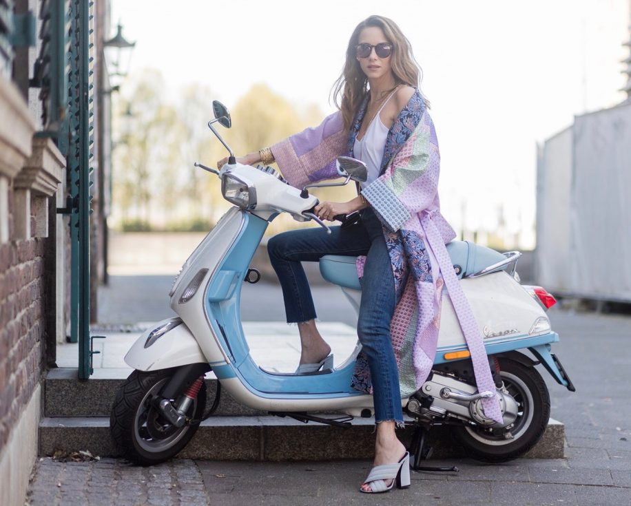Model and fashion blogger Alexandra Lapp wearing a printed kimono / panel robe from Natasha Zinko, slim fit high waist Jeans from Rag & Bone, Mules by Gucci with open-toe-silhouette in glittery silver grey, white silk tank top from Jadicted, colorful mirrored sunglasses from Les Specs, black leather ring detail continental purse bag from Fendi featuring an embossed logo, a press stud fastening, multiple interior card slots, an interior zipped compartment and a gold-tone chain shoulder strap on March 30, 2017 in Duesseldorf, Germany.