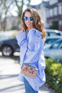 Model and fashion blogger Alexandra Lapp wearing an oversized navy and white striped cotton shirt, cut for an oversized fit with a point collar and dropped shoulders from Vetements, blue jeans from Vetements in cooperation with Levi`s with cut-out raw hems, blue aviator sunglasses from illevesta, Christian Louboutin pumps in cognac, filigree rose gold jewelry from Art Youth Society and a studded embellished crossbody bag from Fendi featuring a foldover top with magnetic closure, an interior zipped compartment, multiple interior card slots and a silver-tone chain shoulder strap on March 30, 2017 in Duesseldorf, Germany.