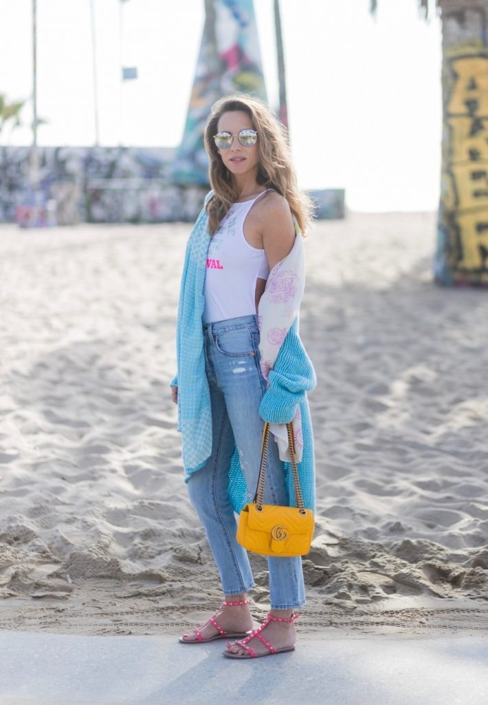 Model and fashion blogger Alexandra Lapp enjoying the beach life, wearing Levis skinny jeans in light blue with a vintage optic, a body from Patrizia Pepe in sensitive white lycra with iridescent and fluorescent laminated Welcome to the Desert Festival print, a long cashmere cardican / coatigan from Heartbreaker in turquoise, a pashmina scarf from Heartbreaker, Valentino Rockstud sandals in pink, a yellow Gucci GG Marmont bag, silver mirrored sunglasses by Le Specs, IWC Da Vinci Automatic 36 watch in 18-carat red gold with diamonds and jewelry from AYS (Art Youth Society) in Venice Beach on April 19, 2017 in Los Angeles, California.