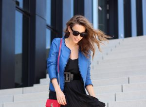 Model and Blogger Alexandra Lapp wearing a blue leather jacket from Riani, high waist pleated skirt by Givenchy, black silk top from Jadicted, a black lacquer waist belt from Dolce & Gabbana, big cat-eye 'Audrey' sunglasses from Céline, a red crossover purse bag from Patrizia Pepe and 'Harler' 100cm calf multicolor high heels from Christian Louboutin with a red sol, red front, black back and a blue little belt around the ankles, on June 2017 in Duesseldorf.