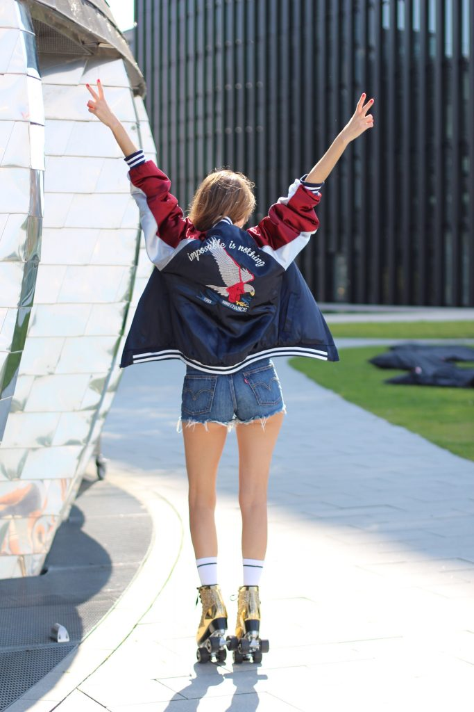 Model and Blogger Alexandra Lapp wearing golden, sparkling Roller Skates from Cosmoparis, mother-fucker socks from Mother Denim, Jadicted silk top in white, Levi's fringed denim high waist shorts, Stylenanda bomber jacket with an embroidered eagle and the letters 'Nothing is impossible' on the back of the three tone jacket in blue, white and red & Thom Browne aviator sunglasses in gold with red, in Duesseldorf on June, 2017.