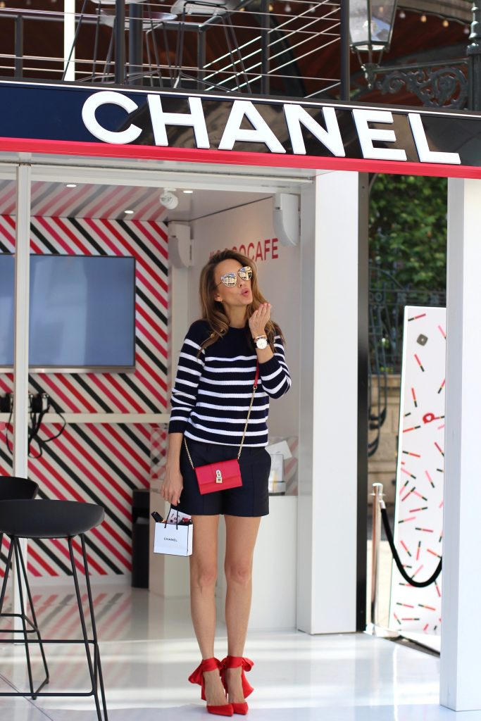 Model and Blogger Alexandra Lapp sitting at Coco Café #cococafe in Duesseldorf, wearing a blue white striped cashmere pullover with gold buttons from Heartbreaker, a dark blue silk shorts by Prada, satin Douce du desert pumps in red with a big silk bow from Christian Louboutin, red crossover purse-bag from Patrizia Pepe and gold cat-eye sunglasses from KARL by Karl Lagerfeld, in Duesseldorf on June, 14th 2017.