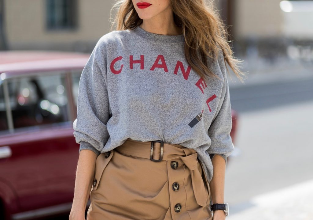 Alexandra Lapp (model, blogger) wearing a vintage sweater from Chanel in grey melange, printed with Chanel red capital letters, a red lipstick and a powder box from Chanel, a midi skirt in a trench silhouette from Self-Portrait, with beige cotton and utilitarian buttons, a belt and a asymmetric cut with a thigh-high slit, red Christian Louboutin pumps in crepe de satin, MCM Milla Spanish leather Tote bag and black Celine Audrey sunglasses during the Mercedes-Benz Fashion Week Berlin Spring/Summer 2018 on July 6, 2017 in Berlin, Germany. (Photo by Christian Vierig)