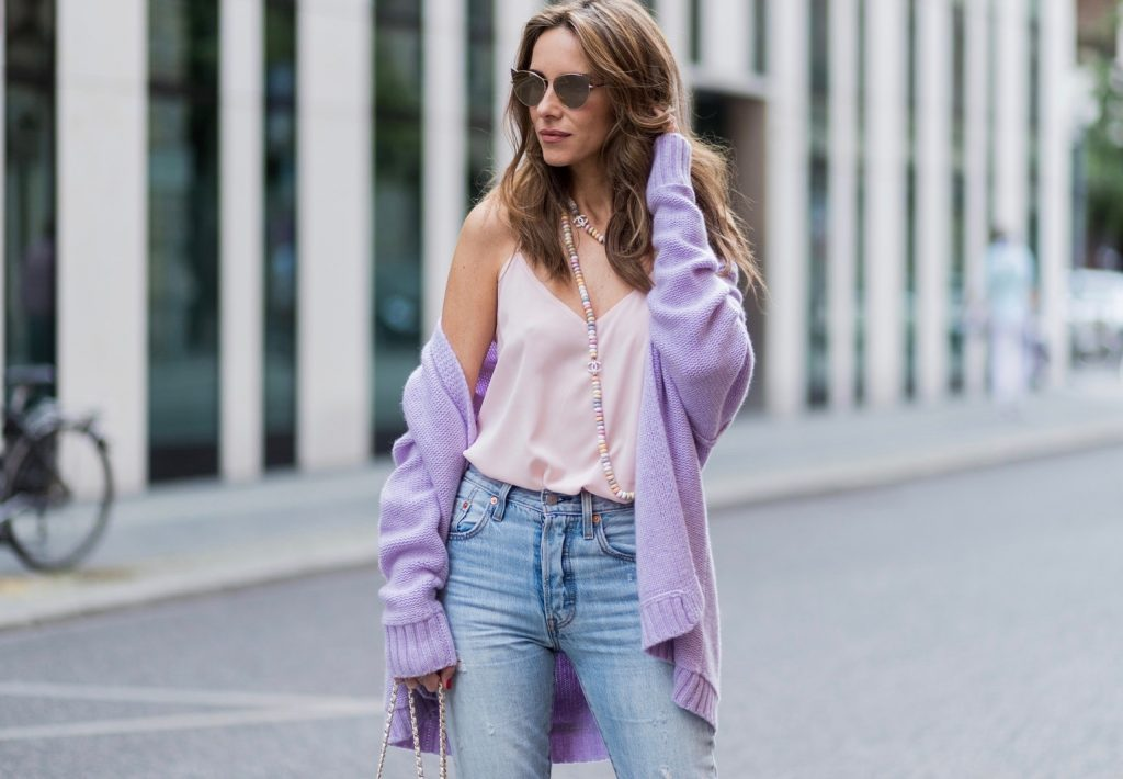 Alexandra Lapp wearing a pastel purple look, a purple cashmere cardigan by Heartbreaker, a rose tank top in silk from Jadicted, a high waist, non-strech denim, five-pocket 501 skinny jeans from Levis, a candy necklace from Chanel supermarket collection in pastel tones, a Chanel perfume bottle bag in plexiglass and a golden chain with white leather, Christian Louboutin pumps Feerica with nude mesh upper embedded with a Swarovski crystal degrade and Karl Lagerfeld cat-eye sunglasses in the shape of cat ears during the Mercedes-Benz Fashion Week Berlin Spring/Summer 2018 on July 7, 2017 in Berlin, Germany.
