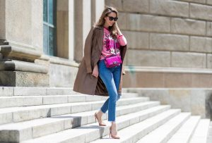 Alexandra Lapp wearing a leather coat in cognac by Riani, a round neck pullover, printed with BAM in comic style and pailettes, Levis Wedgie Icon Fit jeans in slim fit and dark blue, a Boy bag in metallic pink patent leather, Gucci sunglasses and cognac So Kate high heels from Christian Louboutin during the Mercedes-Benz Fashion Week Berlin Spring/Summer 2018 on July 7, 2017 in Berlin, Germany.