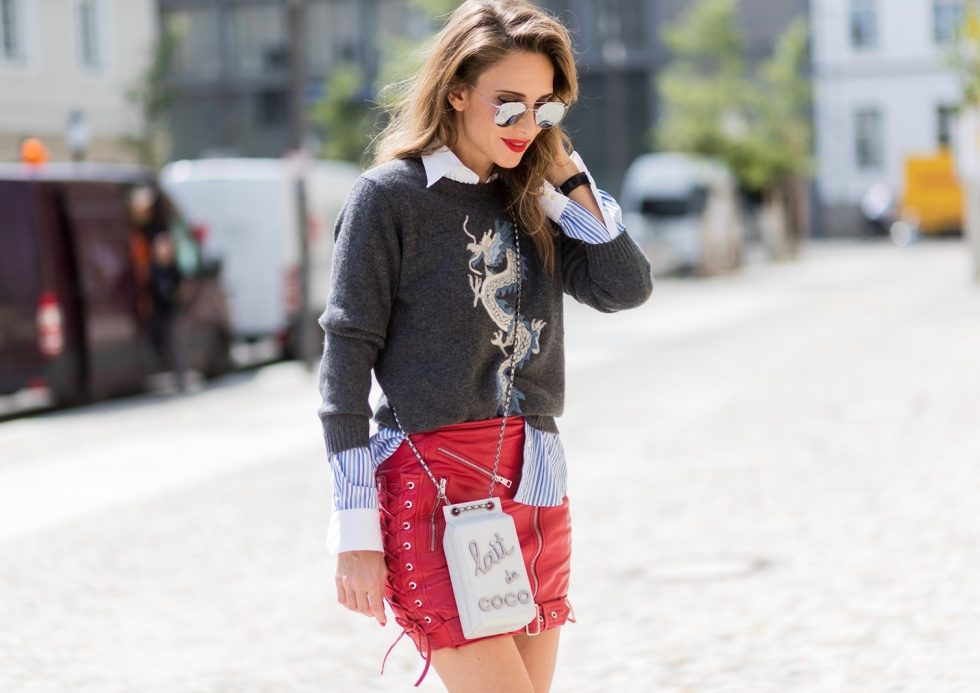 Alexandra Lapp (model, blogger) wearing a cashmere pullover with a Chinese Dragon from Heartbreaker in cashmere, a grey cashmere scarf by Heartbreaker, a blue-white striped shirt from Etro, rocking Biker skirt with zippers in silver, a red lambskin leather skirt, zip front closure, front zip pockets and lace up detail on sides, red patent leather pumps from Gianvito Rossi, the Chanel Milk Bottle Bag Lait de Coco from 2014, a chain shoulder bag with pearls in silver-grey, in the shape of a milk carton and silver mirrored sunglasses by Le Specs during the Mercedes-Benz Fashion Week Berlin Spring/Summer 2018 on July 6, 2017 in Berlin, Germany.