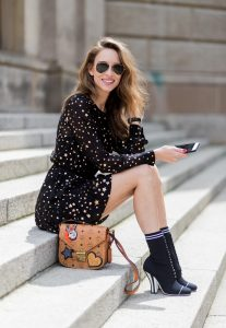 Alexandra Lapp (model, blogger) wearing Fendis SS 17 collection sock boots with a grey knit upper, with a high sculptural heel, a black silk chiffon mini dress with gilded stars from RED Valentino with a tie at the neck and a ruffle through the hem, a MCM Patricia Shoulder Bag crafted in in Visetos-print coated canvas and topped with crystalized appliqués, including the Punk Rabbit, accented with mink fur, studwork and edge painting and a laurel-engraved case latch closure and Ray Ban aviator sunglasses in gold during the Mercedes-Benz Fashion Week Berlin Spring/Summer 2018 on July 6, 2017 in Berlin, Germany.