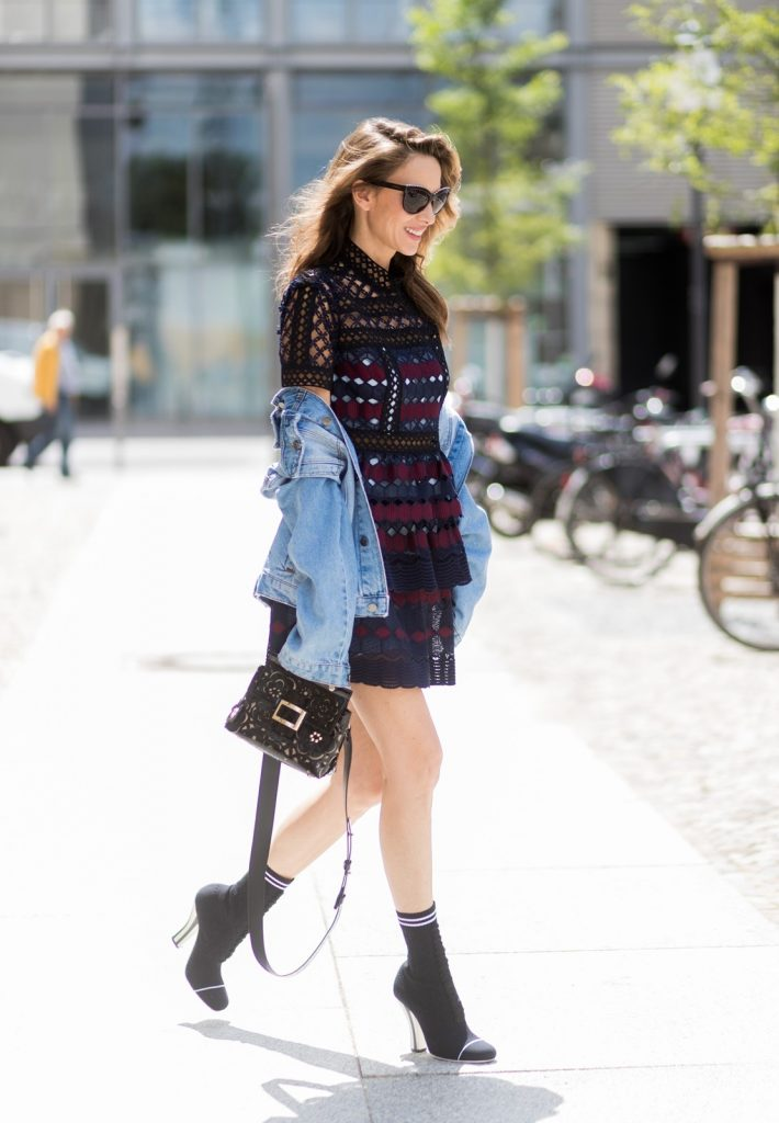 Alexandra Lapp (model, blogger) wearing a mini lace dress in navy blue and heady red from Self-Portrait, a Roger Viv mini bag crafted in suede with waterjet cut Guipure detailing, flap, clasp fastening, metal buckle and details, handle and leather removable strap in trapezium shape and ankle boots from Roger Vivier in black patent leather, denim jacket by SET, brown sunglasses with pearls by Chanel and Fendi during the Mercedes-Benz Fashion Week Berlin Spring/Summer 2018 on July 6, 2017 in Berlin, Germany.