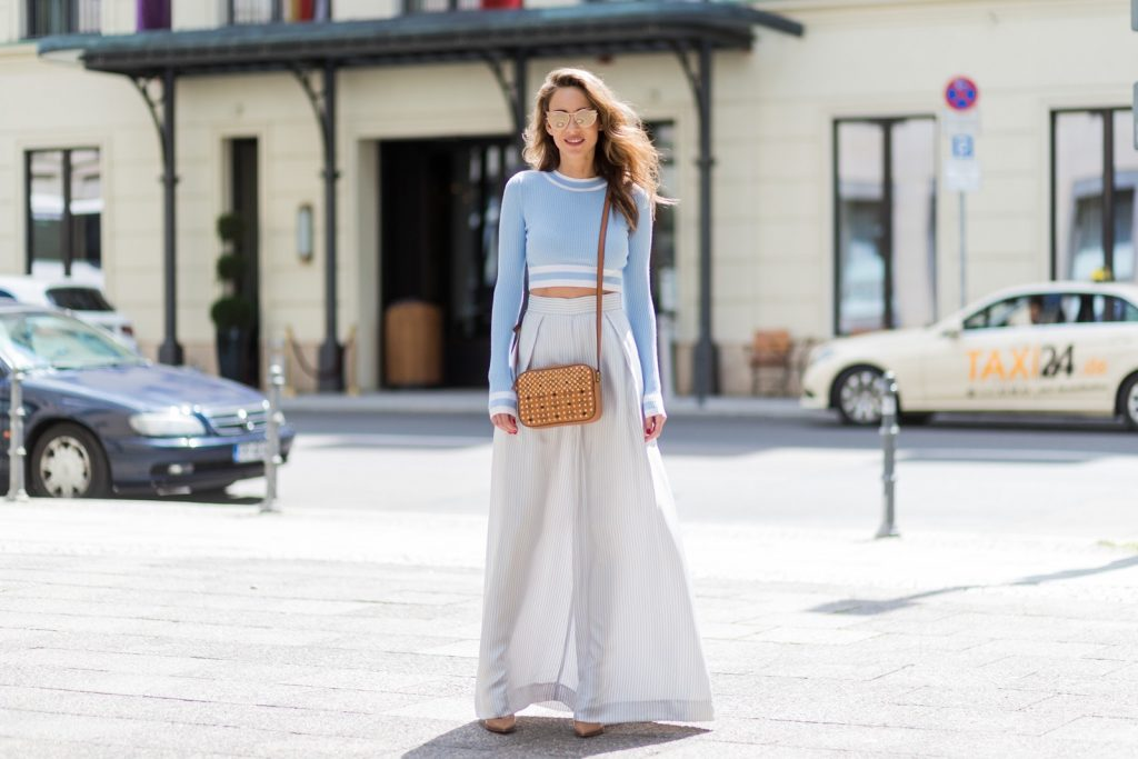 Alexandra Lapp (model, blogger) wearing blue-white striped wide leg pants from Zimmermann, a baby blue cropped top from H&M, gold mirrored cat-eye sunglasses from Karl by Karl Lagerfeld and crossover Diamond Visetos bag from MCM with studs and Swarovsky chrystals on one side and an allover logo print from MCM during the Mercedes-Benz Fashion Week Berlin Spring/Summer 2018 on July 6, 2017 in Berlin, Germany.