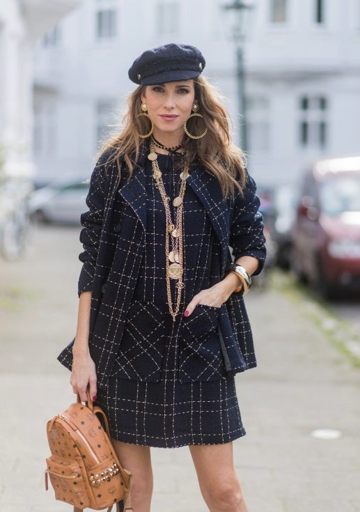 Model and fashion blogger Alexandra Lapp wearing a look inspired by Chanel, a tweed dress and coat from Steffen Schraut, Balmain x HM sandals, Strak backpack by MCM, Chanel tweed cap, golden Chanel chains in form from Chanel coins, Chanel chocker and golden bracelet from Schubart Goldschmiede and golden vintage earrings with a peals by Chanel on August 5, 2017 in Duesseldorf, Germany.