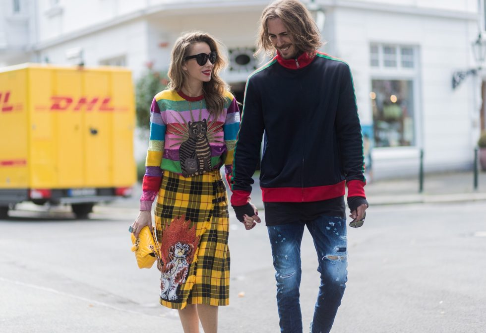 Couple look a like holding hands in front of DHL van - Model and Blogger Alexandra Lapp wearing a Gucci total look, a yellow and red pleated tartan skirt embroidered with a spaniel dog and belt buckle closure, colorful striped sweater with lace and merino with embroidered cat applique all Gucci, black Christian Louboutin So Kate pumps, GG Marmont Gucci bag in yellow, Audrey sunglasses from Celine and Model and Blogger Thomas Stuch wearing classic Kenny Twist Jean from Dsquared, black T-Shirt Thom Krom, Gucci track suit top, Stallion Cowboy Boots on August 4, 2017 in Duesseldorf, Germany.