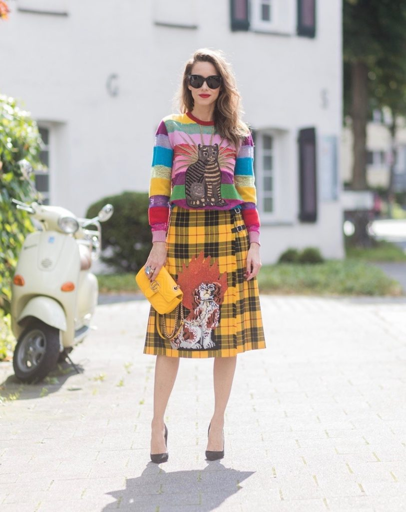 Model and Blogger Alexandra Lapp wearing a Gucci total look, yellow and red pleated tartan skirt embroidered with a spaniel dog and belt buckle closure, colorful striped sweater with lace and merino with embroidered cat applique all Gucci, black Christian Louboutin So Kate pumps, GG Marmont Gucci bag in yellow, Audrey sunglasses from Celine on August 4, 2017 in Duesseldorf, Germany.