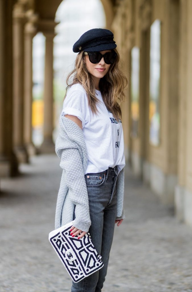 Alexandra Lapp wearing a T-Shirt from H&M, printed with The Revolution Is Female, a high waist, non-strech denim, five-pocket 501 skinny jeans from Levis in grey, Cashmere cardigan in grey, Roger Vivier pumps in a sharp cut and sheeny satin fabric in black and white stripes with crystal flower-embellished buckle at the front and sling-back shape and the 2.55 classic Chanel bag in white leather with black pearls during the Mercedes-Benz Fashion Week Berlin Spring/Summer 2018 on July 7, 2017 in Berlin, Germany.