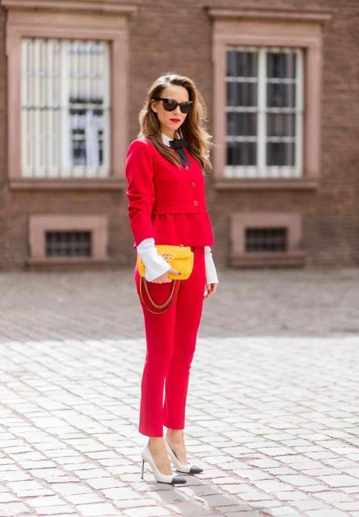Model and fashion blogger Alexandra Lapp wearing a slim fit, red suit from Steffen Schraut, blazer with peplum and red pants, white blouse with a black ribbon bow from Steffen Schraut, white pumps with black toecap from Saint Laurent, Chanel sunglasses with pearls and yellow GG Marmont bag from Gucci on August 5, 2017 in Duesseldorf, Germany.