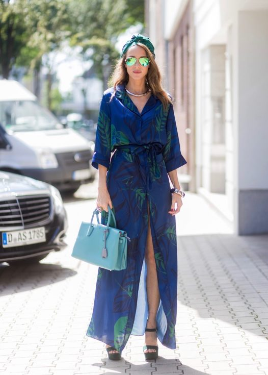 Model and fashion blogger Alexandra Lapp wearing a blue Kimono maxi dress with green leaf print from Borgo de Nor, green metallic Aviator sunglasses by Ray-Ban, plateau heels from Prada, Milla MCM bag in turquoise, a green bandana turban, neck ripe and bracelet in grey gold by Schubart Goldschmiede, three rings in grey gold with a green Tourmaline by Schubart on August 4, 2017 in Duesseldorf, Germany.