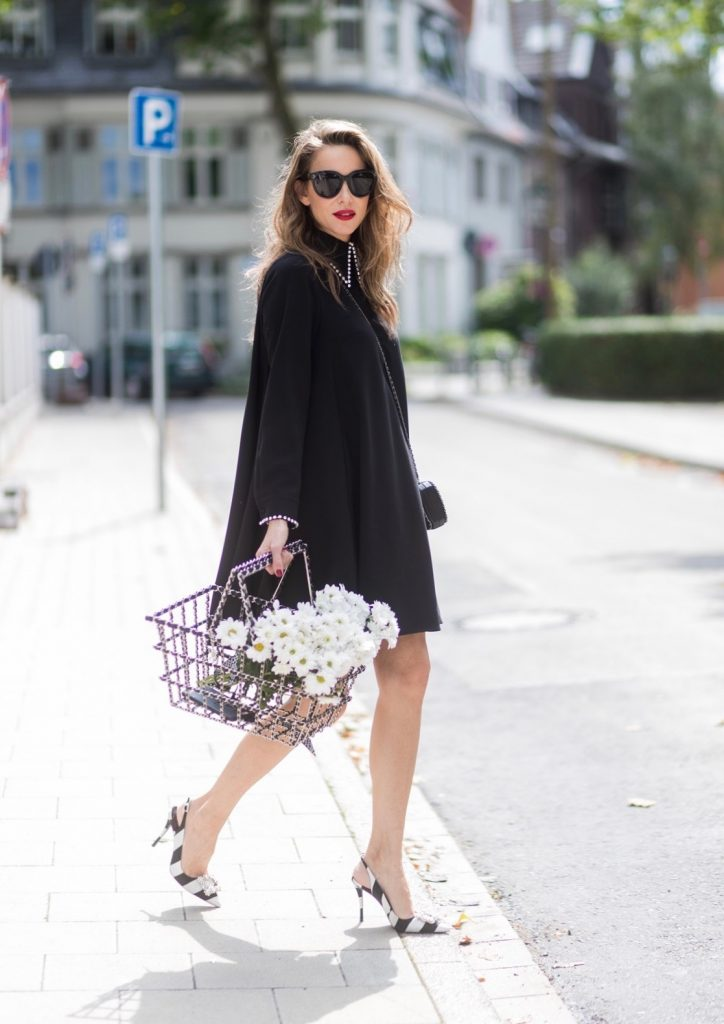 Model and fashion blogger Alexandra Lapp wearing a black shirt dress from Steffen Schraut, Celine Audrey sunglasses, flower satin sling-back pumps with black and white stripes, a shopping basket from Chanel with flowers, black Chanel mini bag on August 4, 2017 in Duesseldorf, Germany.