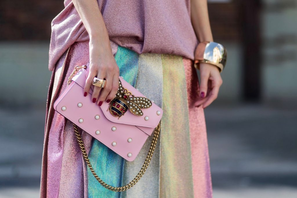 Model and fashion blogger Alexandra Lapp wearing metallic chic, pleated lame skirt in shimmering pastel, pink metallic v-neck knit by Alberta Ferretti, Christian Louboutin Feerica heels with Swarovski crystals and flower accessory, pink Broadway leather bag with pearl studs, Le Specs sunglasses, bracelet and rose gold ring with baguette diamonds by Schubart on August 4, 2017 in Duesseldorf, Germany.