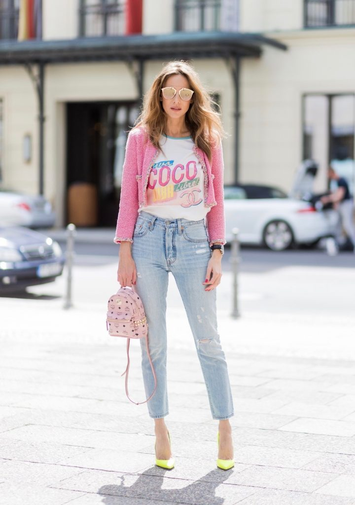 Alexandra Lapp (model, blogger) wearing Stark mini backpack in pink from MCM, Visetos-print coated canvas, a high waist, non-strech denim and five-pocket 501 skinny jeans from Levi's, a graphic Chanel T-Shirt printed with Viva Coco Cuba Libre from Chanel Cuba Cruise 2017 collection, a short vintage tweed jacket in pink from Chanel, Christian Louboutin So Kate pumps in neon yellow and 'Dior Reflected Aviator' sunglasses in gold from Dior during the Mercedes-Benz Fashion Week Berlin Spring/Summer 2018 on July 6, 2017 in Berlin, Germany.