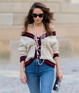 Alexandra Lapp wearing a cashmere cardigan with pearls in beige with a collar in blue and red Levis Wedgie Icon Fit jeans in slim fit and dark blue, a long, pearl necklace from Chanel with the Chanel Logo, brown sunglasses with pearls from Chanel, Fly with Karl clutch from Karl Lagerfeld and cognac So Kate high heels from Christian Louboutin during the Mercedes-Benz Fashion Week Berlin Spring/Summer 2018 on July 7, 2017 in Berlin, Germany.