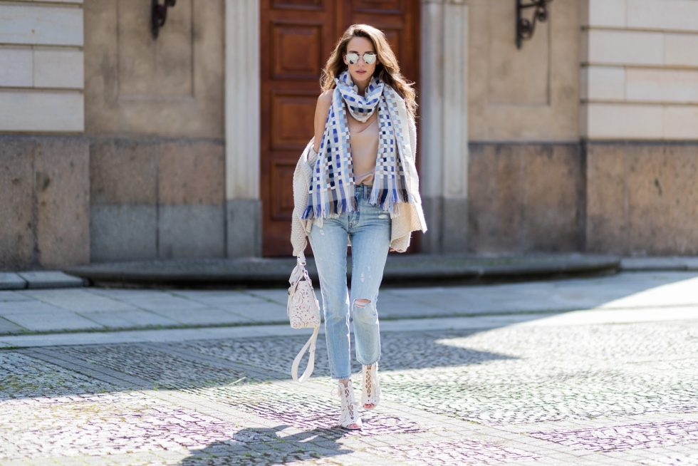 Model and fashion blogger Alexandra Lapp wearing a scarf and beige cashmere cardigan by Heartbreaker, beige tank top in silk from Jadicted, a high waist, non-strech denim, five-pocket 501 skinny jeans from Levis, Roger Vivier Viv bag in leather with removable strap in trapezium shape, ankle boots from Roger Vivier in with floral cutouts and a mirrored block heel and silver mirrored sunglasses from Le Specs during the Mercedes-Benz Fashion Week Berlin Spring/Summer 2018 on July 8, 2017 in Berlin, Germany.