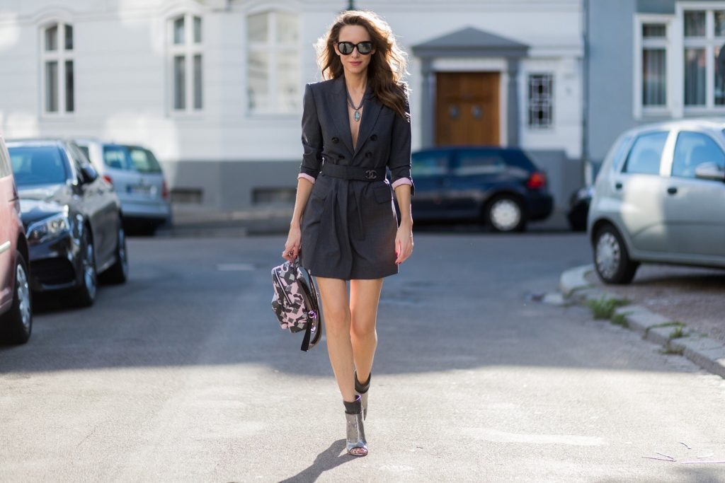 Model and fashion blogger Alexandra Lapp wearing a blazer dress in grey by Dsquared with matching waist belt, Chanel broach, camouflage Stark backpack from MCM, Diormania sunglasses from Dior, Giuseppe Zanotti open-toe ankle booties, pendant in grey gold with topaz and ring in grey gold with aquamarin by Schubart jewelry on August 4, 2017 in Duesseldorf, Germany.