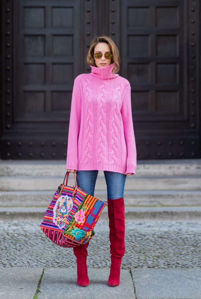 Model and fashion blogger Alexandra Lapp wearing Christian Louboutin folkloric Mexicaba tote in cotton-canvas in collaboration with the Taller Maya Foundation, a pink turtleneck in cashmere from Heartbreaker, red overknees from Gianvito Rossi, Adriano Goldschmied AG Denim Jeans and gold mirrored sunglasses by Thom Browne during the Mercedes-Benz Fashion Week Berlin Spring/Summer 2018 on July 8, 2017 in Berlin, Germany.