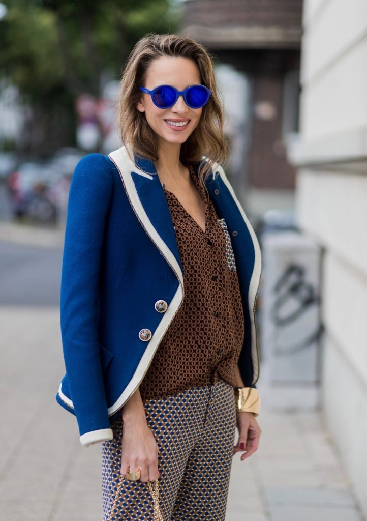 Model and fashion blogger Alexandra Lapp wearing pajama style, silk blouse and pants from Steffen Schraut, blue Balenciaga blazer jacket, blue lacquer pumps from Christian Louboutin, Millie cross body bag in beige from MCM with a golden chain, rose gold bracelet and rose gold ring with baguette diamonds from Schubart Goldschmiede on August 3, 2017 in Duesseldorf, Germany.