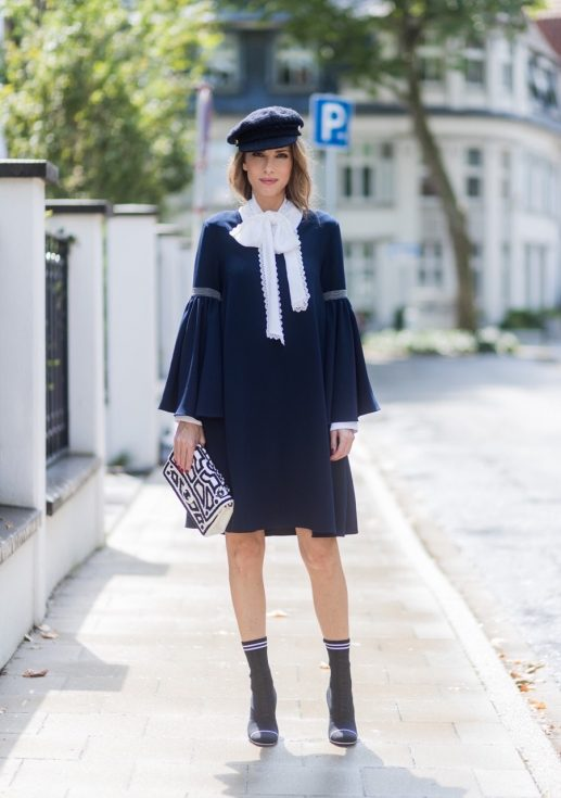 Model and fashion blogger Alexandra Lapp wearing a navy dress with oversized sleeves and a white tie-neck blouse from Steffen Schraut, Chanel tweed cap, baroque Fendi sock-boots in black and white, Chanel 2.55 classic back in white leather with black pearls on August 4, 2017 in Duesseldorf, Germany.